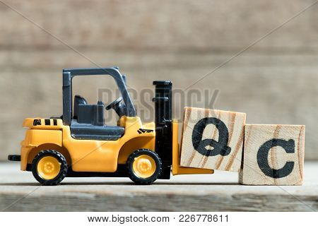 Toy Yellow Forklift Hold Letter Block Q To Complete Word Qc (abbreviation Of Quality Control)on Wood