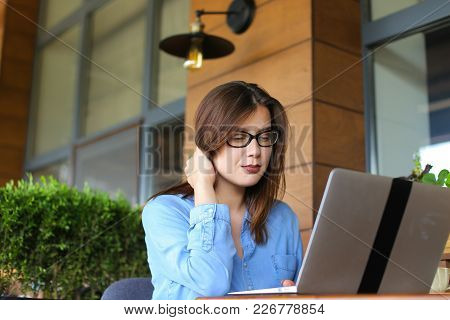 Female Student Chatting With Friends By Laptop At Cafe. Young Girl Dressed In Jeans Shirt Sitting Ne