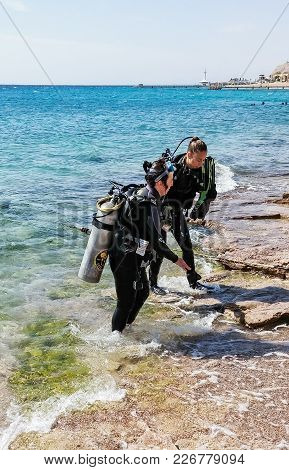 Eilat, Israel, March 13, 2015 : Two Scuba Divers In Suits For Scuba Diving Out Of The Water Near The