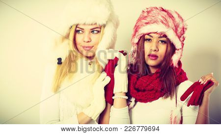 Fashion Winter Outfit Concept. Two Girls Blonde And  In Warm Red White Clothing Portrait. Attractive