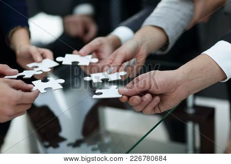 Business people holding jigsaw puzzle.