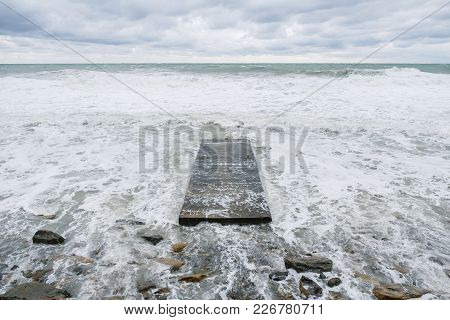 Old Destroyed Pier At Sea Rolls In Like Waves During A Storm.