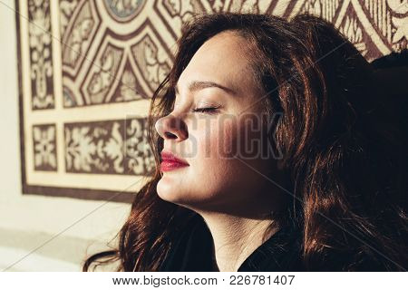Woman enjoying sun in the city. Close-up female portrait. Sunny spring day.