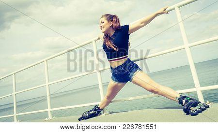 Happy Joyful Young Woman Wearing Roller Skates On Sea. Girl Having Fun During Summer Time.