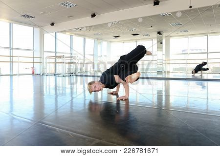 Male Sportsman Preparing Body For Loads And Doing Stretching. Blonde Boy Wears Black Suit And Sittin