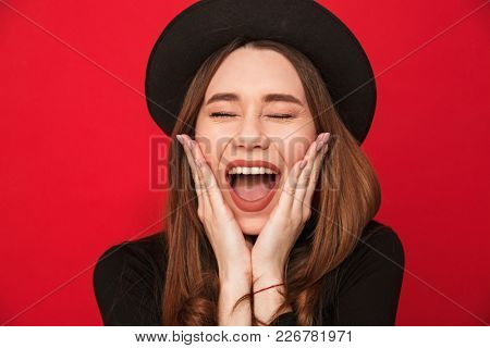 Photo of screaming excited young woman standing isolated over red background.