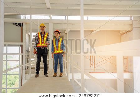 Asian Couple Of Architect, Engineer Or Technician Man And Woman With Safety Helmet Holding Blueprint