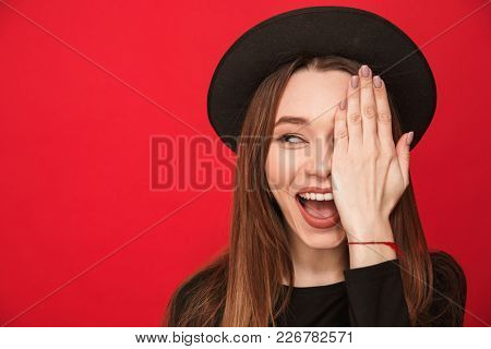Picture of excited young woman standing isolated over red background covering eye with hand looking aside.