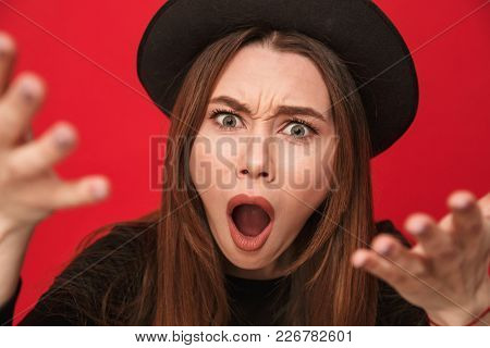 Photo of displeased screaming young woman standing isolated over red background. Looking camera.
