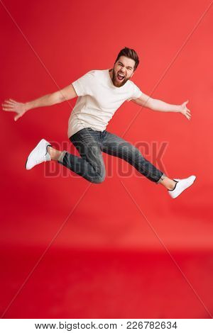 Image of excited emotional bearded man jumping isolated over red background wall looking camera.