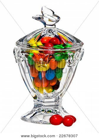 Elegant crystal dish filled with candy and some at base.