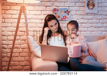 Mother And Little Daughter Watching Movies On Laptop And Eating Popcorn At Night At Home.
