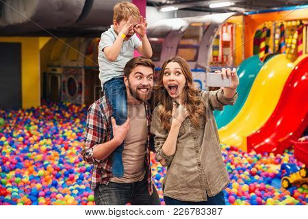 Picture of happy little child have fun with his parents in entertainment game center. Looking aside make selfie by phone showing thumbs up.