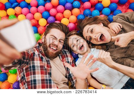 Image of happy little child have fun with his parents in entertainment game center. Looking aside make selfie by phone showing thumbs up.