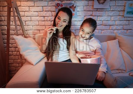 Mother And Little Daughter Watching Movies On Laptop And Eating Popcorn Under Lampshade At Night At