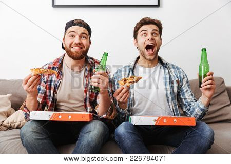 Two agitated emotional men eating pizza and drinking beer with while supporting football team at home