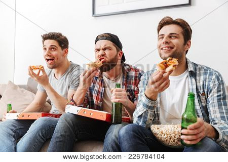 Portrait of three young bachelors eating pizza with pleasure while watching football match at home tv