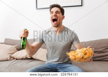 Image of young bachelor shouting happily while resting at home and watching football or basketball game with beer and chips