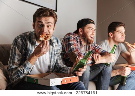 Image of three hungry guys eating pizza with pleasure while attentively watching football match at home