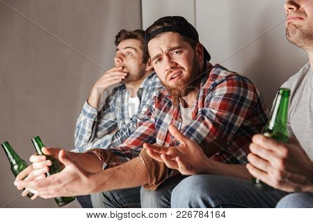 Photo of crushed guys expressing frustration and dissatisfaction while watching football game in flat with bad results
