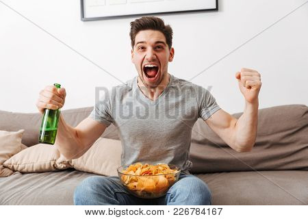 Agitated handsome guy screaming and rejoicing while watching football or basketball game with beer and chips in apartment