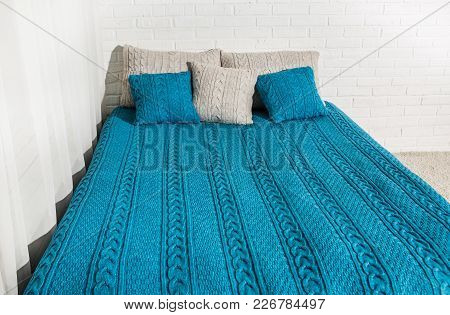 Bed By The Window With A Textured Coverlet And Pillow Cases