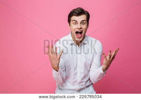 Image of young screaming excited man standing isolated over pink background. Looking camera.