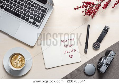 Red Make Your Dreams Come True Writing In Open Notepad With Coffee Mug, Camera, Clock And Laptop Lyi