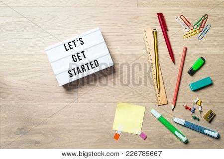 Let's Get Started Written On Lightbox In Office As Flatlay