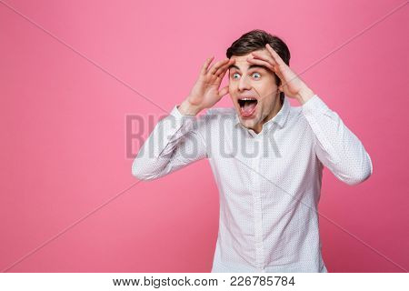 Image of young screaming excited man standing isolated over pink background. Looking aside.