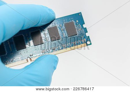 Hand In Blue Glove Holding Ram Memory On White Background