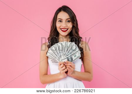 Image of young rich asian woman smiling with white teeth and holding lots of money in dollar currency isolated over pink background