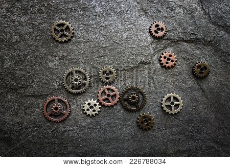 Assorted Gears Spread Out On Textured Background -- Gears Are Not Connected, Could Be Lack Of Coordi
