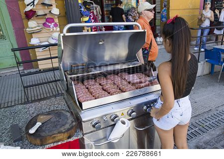 Buenos Aires, Argentina - January 20, 2018: Unindentified Woman Selling Grilled Sausages At Caminito
