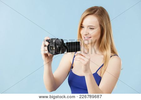 Photographer Girl Shooting Images. Lovely Blonde Smiling Woman With Camera On Blue Background