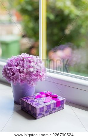 Little Purple Bucket With Tender Bouquet Of Beautiful Pink Carnation With Violet Gift Box Near Windo