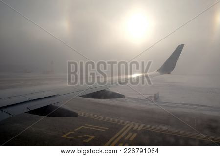 Passenger Plane Takes Off From The Runway Aerodrome With Road Marking In Winter In Bad Weather Condi
