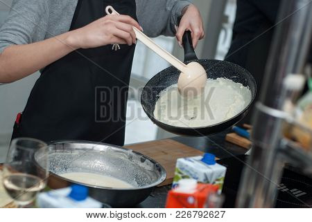 Process Of Making Traditional Thin Pancakes In A Frying Pan.