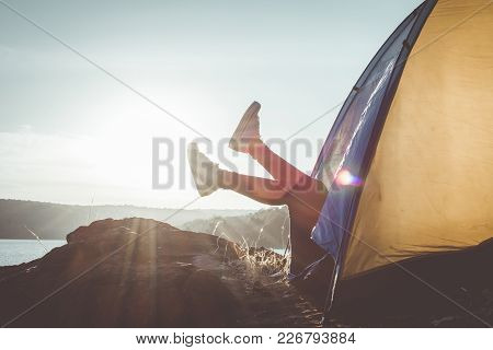 Silhouette Feet Woman Relaxing In Tent During Camping, Concept Travel And Camping ,selective And Sof