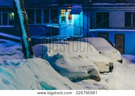 Cars Stand In The Yard In The Evening Covered With Snow