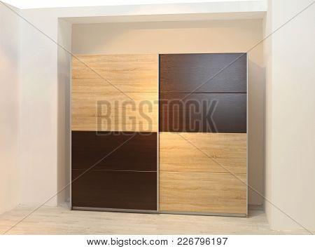 Big Wardrobe Closet With Wooden Doors In Bedroom