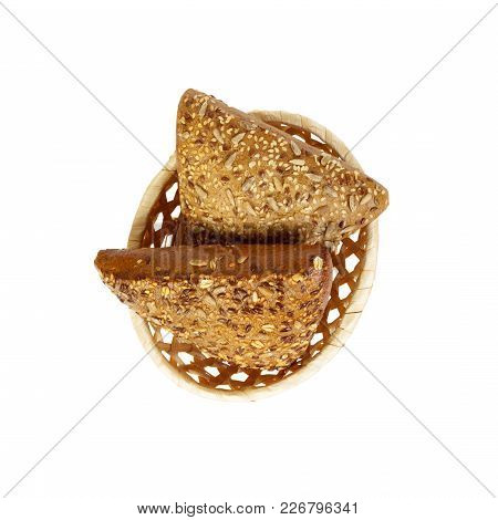 Rye Triangle Bun Sprinkled With Sunflower And Flax Seeds On Basket At White Background, Isolated. To