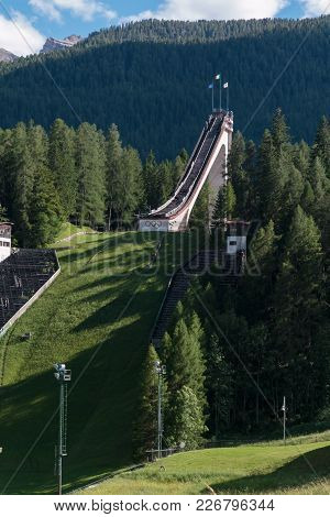 Cortina, Italy - June 2016: Abandoned Olympic Ski Jumping Trampoline Among Mountains Scenery In Summ