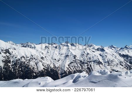 Snow Covered Mountains And Blue Clear Sky At Sun Cold Day. View From Region Dombay, Caucasus Mountai
