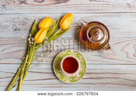 A Cup With Herbal Tea, A Teapot And A Bouquet Of Yellow Tulips On A Wooden Table Close-up.