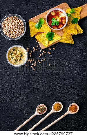 Hummus Ready To Eat. Bowl With Dish Among Pieces Of Crispbread And Spices On Black Background Top Vi