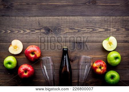 Apple Cider. Low-alcoholic Beveradge In Dark Bottle Near Beer Glasses And Fresh Apples On Dark Woode