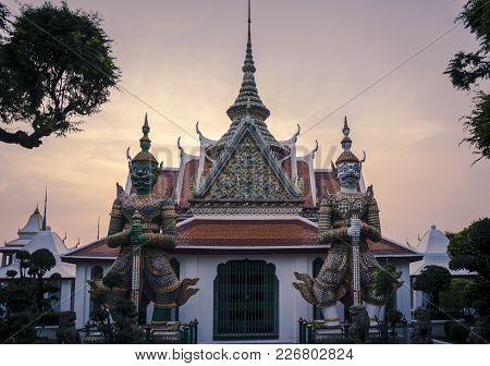 Giant Demons Guarding An Exit In Wat Arun In Bangkok, Thailand