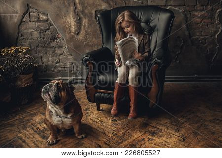 Child Girl In Image Of Sherlock Holmes Sits In Armchair And Reads Newspaper Next To English Bulldog