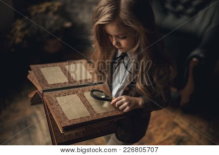 Child Girl In Image Of Sherlock Holmes Stands In Room And Looks Old Photoalbum With Magnifier In Her